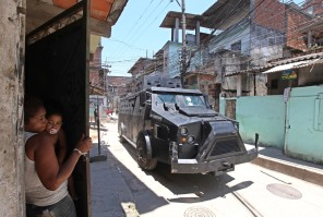 A resident holding a baby hides behind a door as an armored police vehicle patrols during an operation at the Complexo do Alemao slum in Rio de Janeiro, Brazil, Sunday, Nov. 28, 2010. Rio's most dangerous slum that was the backbone of the city's biggest drug gang was taken by 2,600 police and soldiers Sunday, an unprecedented accomplishment by authorities in their fight to secure this seaside metropolis that will host the 2016 Olympics. (AP Photo/Andre Penner)