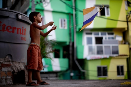 In this photo taken Dec. 17, 2010, Gustavo Nascimento da Silva, 5, flies his kite at the Santa Marta slum in Rio de Janeiro, Brazil. In 2008 police stormed Santa Marta to evict the dealers as the community became the pilot in a program to root out gangs and bring government services to slums long abandoned by the state. The program has since been replicated in a dozen slums, all in a bid to make one of the world's more dangerous cities safer before the 2014 World Cup and the 2016 Olympics. (AP Photo/Felipe Dana)