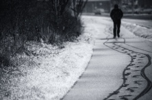 A man walks along a snow footpath in Aberystwyth, image by Craig Kirkwood