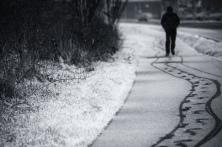 A man walks along a snow footpath in Aberystwyth, image by Craig Kirkwood